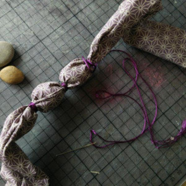 Un collier de cailloux- Enrouler du fil à broder autour des cailloux