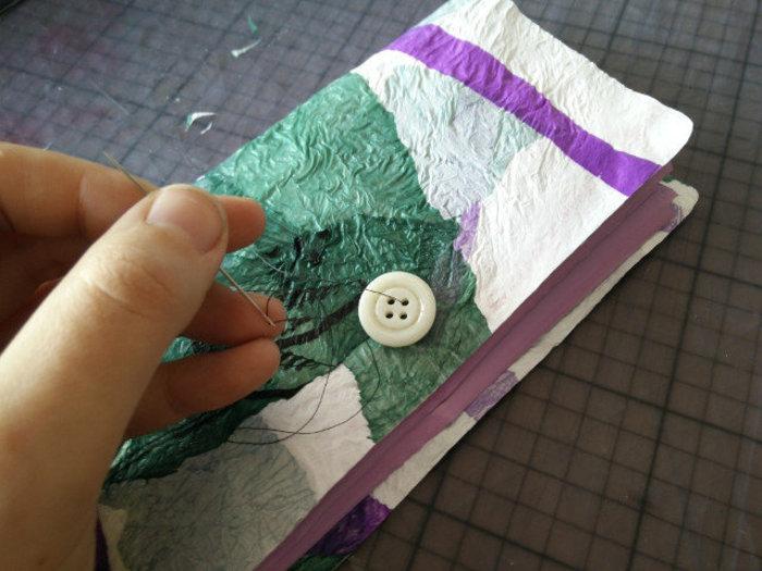 Un portefeuille en sacs plastiques fusionnés- Attacher un bouton et un ruban pour la fermeture du portefeuille