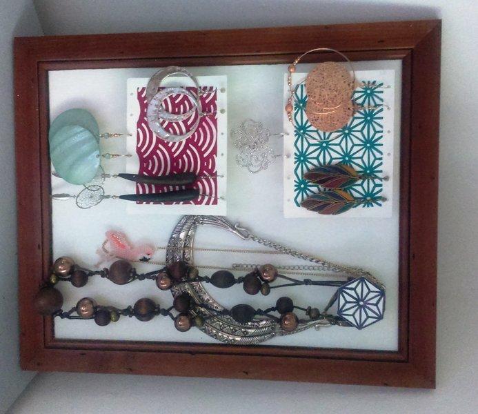 Un porte-bijoux mural en plastique dingue -Mettre le fond en carton dans le cadre et voilà !