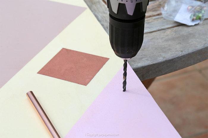 Un organiseur mural graphique et cuivré-Fixer des tubes en cuivre comme supports pour suspensions