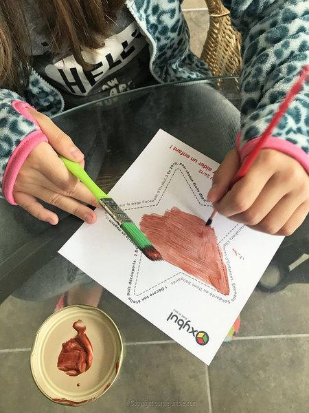 Une suspension murale pour Noël-Peindre les étoiles en papier