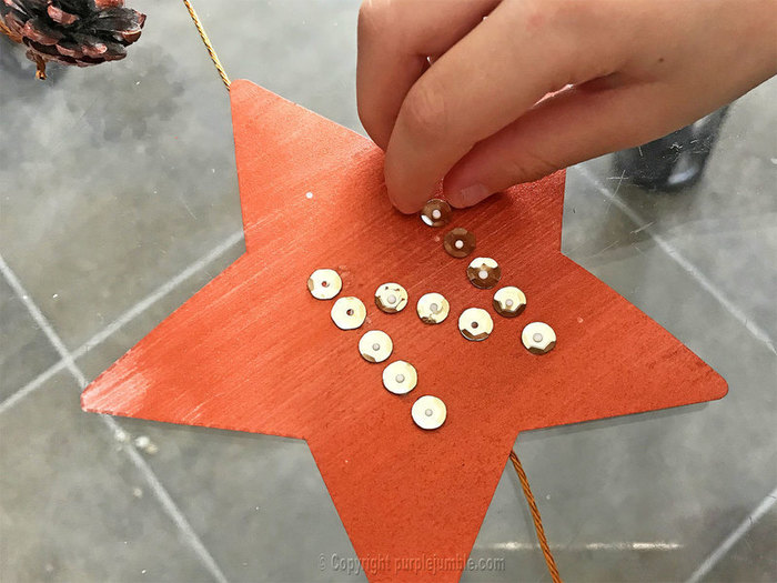 Une suspension murale pour Noël-Décorer les étoiles : écrire Noël avec des sequins
